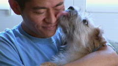 Young Asian man playing with pet dog Stock Footage