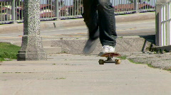Young Asian man skateboarding down sidewalk Stock Footage