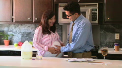 Happy pregnant couple caressing belly in kitchen Stock Footage