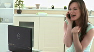 Excited woman phoning and using her laptop Stock Footage