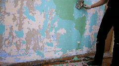 Worker clear wall with trowel from old paint - stock footage