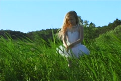 Little blonde girl standing in tall grass Stock Footage