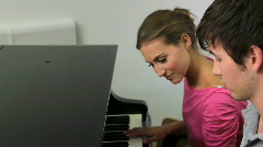 Two students learning how to play piano Stock Footage