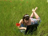 Girl lying on the grass using laptop Stock Footage