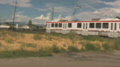 Train goes by a field near the trax as the wind blows Stock Footage