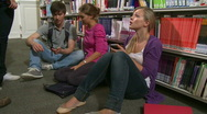Group of students in library chatting and playing with mobile phones Stock Footage