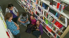Group of student talking between bookshelves in library Stock Footage