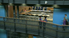 Two female students texting in corridor of university classroom Stock Footage