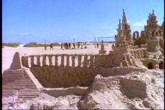 Sand sculpture on beach, sand castle, towering, pan right Stock Footage