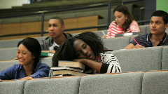 Female student falling asleep on books in lecture theatre, during class Stock Footage