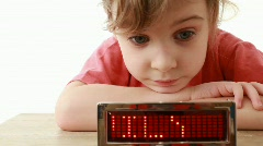 Girl lays on table near information LED display with word Family and smiles Stock Footage