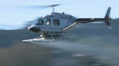 Spraying helicopter banks and turns Stock Footage