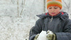 Boy makes and throws snowball in winter forest Stock Footage