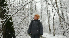 Kid shakes branch of winter tree snow falls down Stock Footage