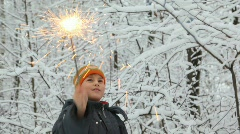 Boy plays with sparkler waves it in winter forest Stock Footage