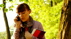 Female student talking on cellphone, outdoors, dolly shot - stock footage