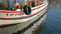 Anchored fisherman's boat floating in the still rippled sea and it's reflexion - stock footage