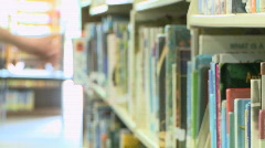 Hand reaches for book on shelf Stock Footage