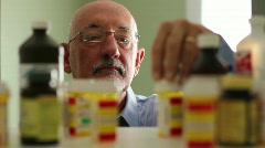 Older man choosing pills from medicine cabinet Stock Footage