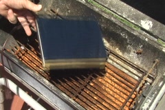 Man places book in barbecue grill to burn it Stock Footage