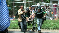 News Reporters JOURNALISTS carry wounded soldier civil war casualty Bangkok 2010 Stock Footage