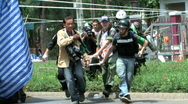 Stock Video Footage of News Reporter JOURNALIST carry wounded soldier war casualty Bangkok April 2010