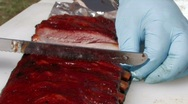 Cutting simmering barbecue ribs ready for serving Stock Footage