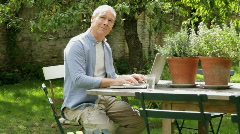 Mature male at table in garden working on laptop computer Stock Footage