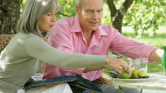 Mature couple in garden eating and looking at photo album memories Stock Footage