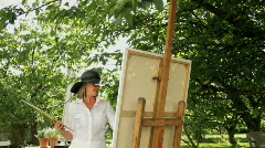 Female painting in domestic garden Stock Footage