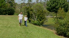 Two Brothers Walk By Pond Stock Footage