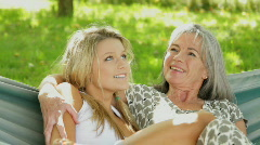 Mother and daughter talking in hammock in garden Stock Footage