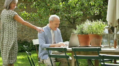 WS, Senior couple at table in garden looking at laptop computer Stock Footage