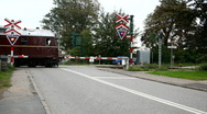 Traincrossing with old train passing Stock Footage