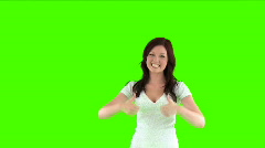 Woman doing a thumbs up against a green screen Stock Footage