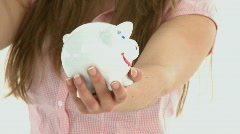 Close-up of woman putting money in a piggybank Stock Footage
