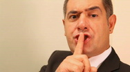 Businessman with finger on lips Stock Footage