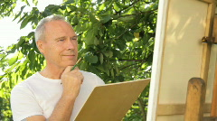 Male painting in domestic garden Stock Footage