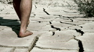 Stock Video Footage of man`s feet on cracked desert earth