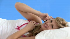 Pleased woman talking on phone lying on a bed - stock footage