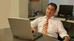 Tired businessman using laptop in office - stock footage
