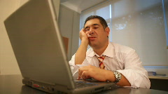 Sleepy businessman using laptop in office Stock Footage