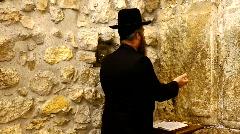 Orthodox Jewish Rabbi prays at the Western Wall in Jerusalem, Israel Stock Footage
