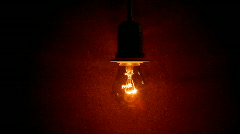 Close up of  filament of an electric light bulb glowing on and off. Stock Footage