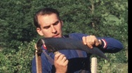 Man sharpening scythe (vintage 8 mm amateur film) Stock Footage