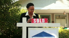 Real estate agent putting up sold sign Stock Footage