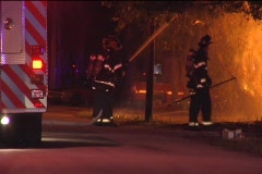 CU Firemen Hose Flames from Street Stock Footage