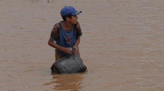 Brazil: Boy collects water from muddy lake. Stock Footage
