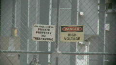 Private Property and High Voltage Warning Signs on a Fence 1 Stock Footage