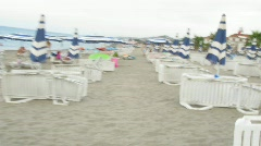 Camera quickly moves on a beach between chaise lounges and umbrellas. Stock Footage